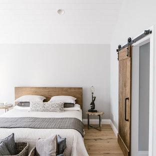 Réalisation d'une chambre champêtre avec un mur gris, un sol en bois clair et un sol beige.