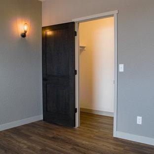 Imagen de dormitorio principal, industrial, grande, con paredes beige, suelo vinílico y suelo marrón