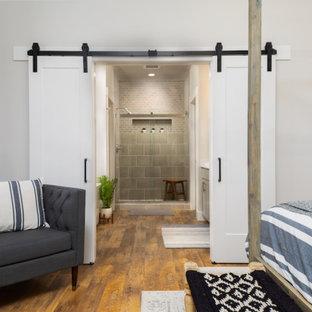 Modelo de dormitorio principal, de estilo de casa de campo, de tamaño medio, con paredes grises, suelo vinílico y suelo marrón