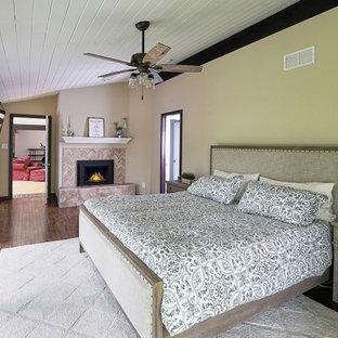 Ejemplo de dormitorio principal, tradicional renovado, grande, con paredes amarillas, suelo de madera en tonos medios, chimenea de doble cara, marco de chimenea de baldosas y/o azulejos y suelo marrón