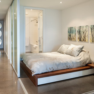 Trendy concrete floor bedroom photo in Vancouver with white walls