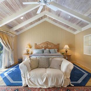 Ejemplo de dormitorio principal, exótico, de tamaño medio, con paredes beige, suelo de baldosas de terracota, chimenea tradicional, marco de chimenea de yeso y suelo multicolor
