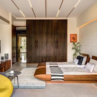 Immagine di una camera matrimoniale etnica con pareti bianche, pavimento in cemento e pavimento grigio