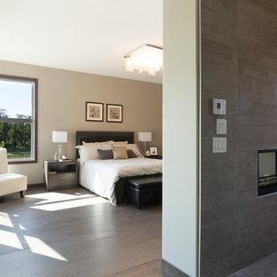 Immagine di una camera da letto design con pareti marroni, camino bifacciale, cornice del camino piastrellata e pavimento marrone