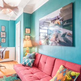 Inspiration pour une chambre bohème de taille moyenne avec un mur vert, un sol en bois clair et aucune cheminée.