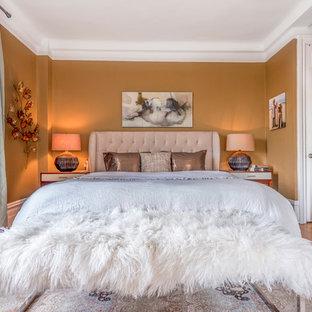 Inspiration pour une grande chambre mansardée ou avec mezzanine bohème avec un mur jaune, un sol en bois clair et aucune cheminée.
