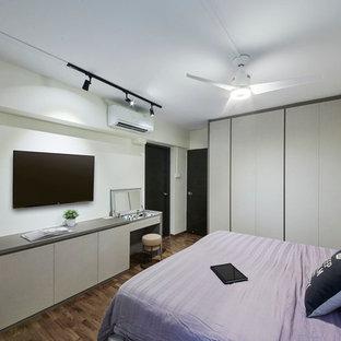 Immagine di una camera matrimoniale minimal di medie dimensioni con pareti bianche e pavimento in compensato