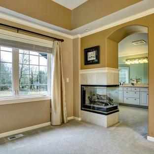 Imagen de dormitorio principal, de estilo americano, grande, con paredes beige, moqueta, chimenea de doble cara y marco de chimenea de baldosas y/o azulejos