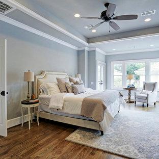ヒューストンの巨大なカントリー風おしゃれな主寝室 (グレーの壁、無垢フローリング、茶色い床、格子天井、グレーの天井)