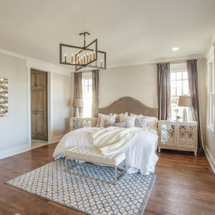Inspiration for a transitional medium tone wood floor and brown floor bedroom remodel in Nashville with beige walls