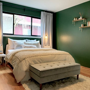 Design ideas for a mid-sized midcentury guest bedroom in San Francisco with green walls, light hardwood floors, no fireplace and brown floor.