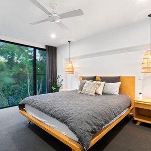 Design ideas for a large beach style master bedroom in Sunshine Coast with white walls, carpet and grey floor.