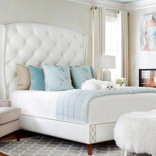 Modelo de dormitorio principal, clásico renovado, grande, con paredes blancas, suelo de madera en tonos medios, chimenea de doble cara y marco de chimenea de piedra
