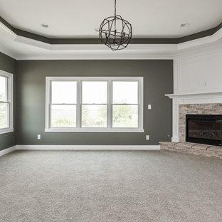 Ispirazione per una grande camera matrimoniale stile americano con pareti grigie, moquette, camino ad angolo e cornice del camino piastrellata