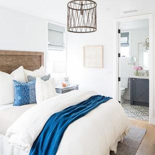 Coastal light wood floor and beige floor bedroom photo in Orange County with white walls