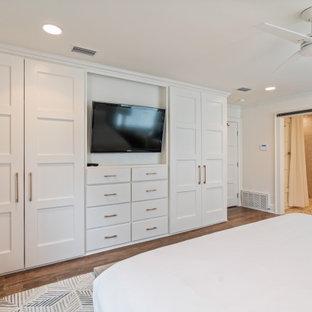 Diseño de dormitorio marinero, de tamaño medio, con paredes blancas, suelo de madera en tonos medios, chimenea de doble cara, marco de chimenea de yeso y suelo gris