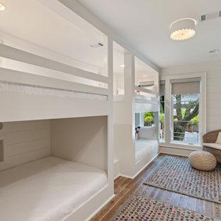 Идея дизайна: спальня среднего размера в морском стиле с белыми стенами, паркетным полом среднего тона, двусторонним камином, фасадом камина из штукатурки и серым полом