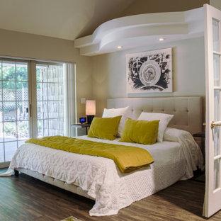 Immagine di una camera matrimoniale design di medie dimensioni con pareti beige, pavimento in laminato, camino lineare Ribbon, cornice del camino piastrellata e pavimento nero
