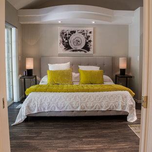 Esempio di una camera matrimoniale minimal di medie dimensioni con pareti beige, pavimento in laminato, camino lineare Ribbon, cornice del camino piastrellata e pavimento nero