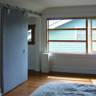 This is an example of a medium sized urban master bedroom in Seattle with white walls and medium hardwood flooring.