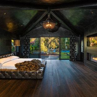 ロサンゼルスのコンテンポラリースタイルのおしゃれな主寝室 (黒い壁、濃色無垢フローリング、横長型暖炉、コンクリートの暖炉まわり、茶色い床)