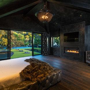 Diseño de dormitorio principal, actual, con paredes negras, suelo de madera oscura, chimenea lineal, marco de chimenea de hormigón y suelo marrón