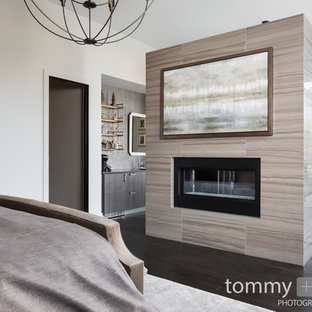 Large transitional master bedroom in Birmingham with grey walls, dark hardwood floors, a two-sided fireplace, a tile fireplace surround and brown floor.