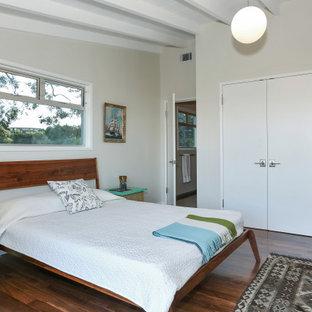 Midcentury bedroom in Los Angeles with beige walls, dark hardwood floors and brown floor.
