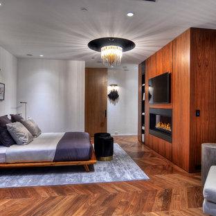 Ispirazione per una grande camera matrimoniale contemporanea con camino sospeso, pareti bianche, pavimento in legno massello medio e pavimento marrone