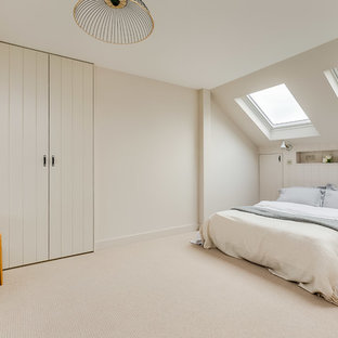 Design ideas for a medium sized scandinavian guest bedroom in London with beige walls, carpet and beige floors.