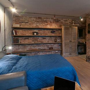 Foto di una camera matrimoniale industriale con pareti marroni e pavimento in legno massello medio