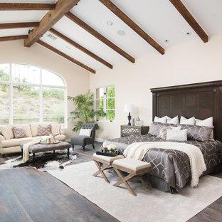 Example of a large tuscan master dark wood floor and brown floor bedroom design in Phoenix with beige walls
