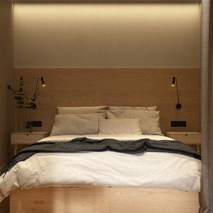Modern inredning av ett litet huvudsovrum, med beige väggar, ljust trägolv och gult golv