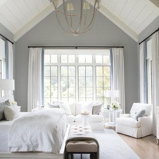 Inredning av ett maritimt sovrum, med grå väggar, ljust trägolv och brunt golv