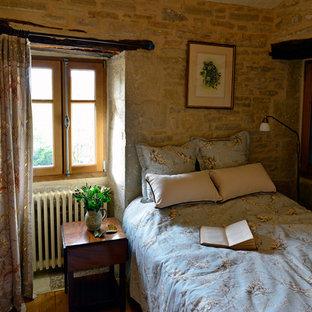 Exemple d'une chambre parentale nature de taille moyenne avec un mur multicolore et un sol en bois brun.