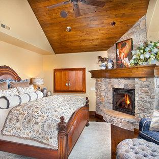 Imagen de dormitorio rural con paredes beige, suelo de madera en tonos medios, marco de chimenea de piedra y chimenea de esquina
