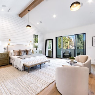 Design ideas for a country bedroom in Los Angeles with white walls, medium hardwood flooring, a ribbon fireplace, a tiled fireplace surround and brown floors.