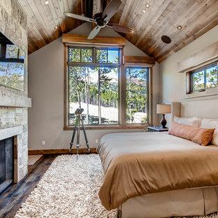 Diseño de dormitorio rústico con paredes beige, suelo de madera oscura, chimenea tradicional y marco de chimenea de piedra