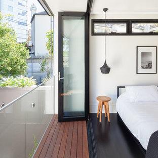 Ispirazione per una camera da letto design con pareti bianche e pavimento nero