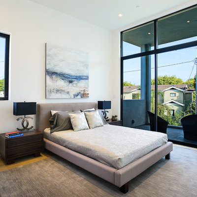 Example of a large trendy master light wood floor and brown floor bedroom design in Los Angeles with white walls and no fireplace