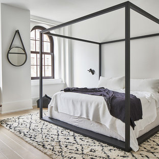Photo of a scandi master bedroom in New York with white walls, light hardwood flooring, no fireplace and beige floors.