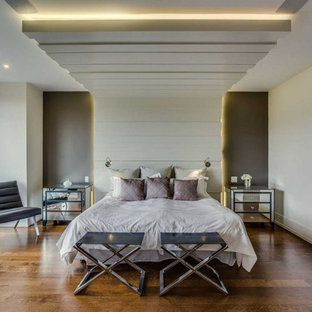 Inspiration for a large modern master medium tone wood floor bedroom remodel in Toronto with white walls and no fireplace