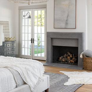 Foto di una grande camera matrimoniale country con pareti bianche, parquet chiaro, camino classico, cornice del camino in cemento e pavimento marrone