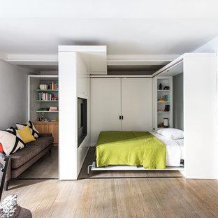 Modelo de dormitorio contemporáneo, pequeño, con paredes blancas y suelo de madera en tonos medios