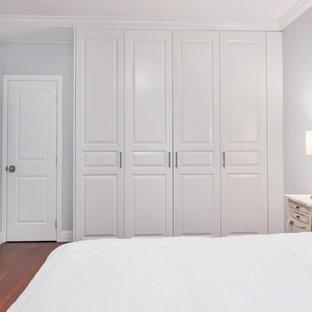 Стильный дизайн: маленькая хозяйская спальня в стиле современная классика с белыми стенами, темным паркетным полом, стандартным камином и фасадом камина из штукатурки - последний тренд