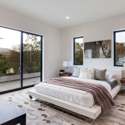Trendy light wood floor and beige floor bedroom photo in Los Angeles with white walls