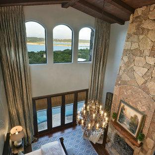 Idee per un'ampia camera matrimoniale mediterranea con pareti grigie, parquet scuro, camino classico e cornice del camino in pietra
