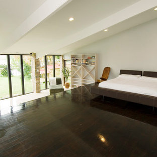 Example of a trendy loft-style dark wood floor bedroom design in New Orleans with white walls