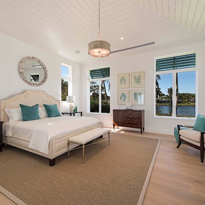 Example of a beach style master light wood floor bedroom design in Miami with white walls