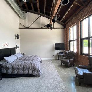 Großes Industrial Schlafzimmer im Loft-Style mit grauer Wandfarbe, Betonboden, grauem Boden, gewölbter Decke und Ziegelwänden in Kansas City